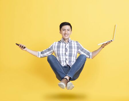 young man holding phone and floating in the air