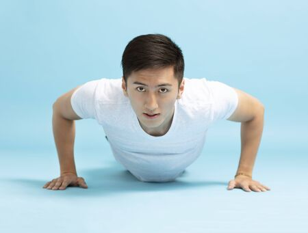 Portrait of young fitness man doing push up
