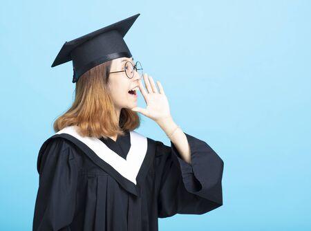 glückliches Abschlussmädchen, das mit Geste schreit
