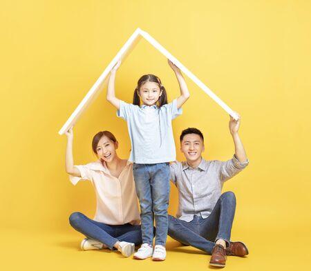 지붕 개념이 있는 새 집에서 행복한 아시아 가족