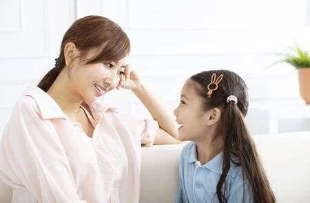 happy mother talking with little girl at home