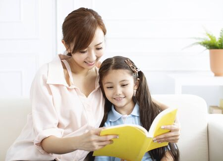 feliz madre estudiando con niña en casa
