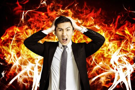 angry young business man with burning fire background Banco de Imagens