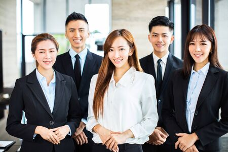 confident asian business team stands in office