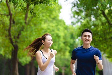 happy asian Couple jogging and running in nature Stock Photo