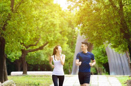 幸せなカップルジョギングと自然の中で実行 写真素材