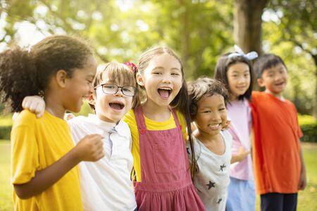 Multi-etnische groep schoolkinderen die lachen en omhelzen Stockfoto