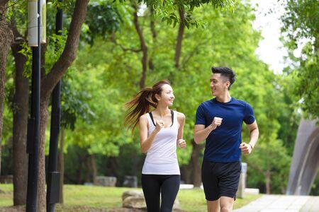 幸せな若いカップルジョギングと公園で走る