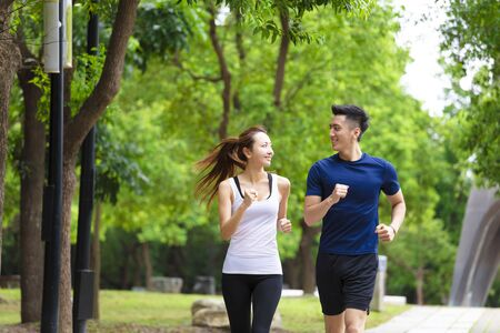 happy young Couple jogging and running  in park Banco de Imagens - 127493174