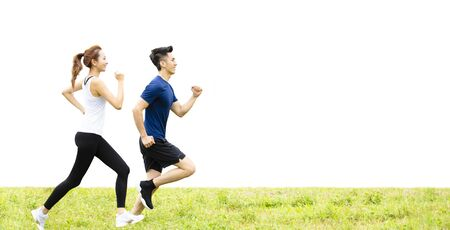 side view of young couple running on the grass 스톡 콘텐츠