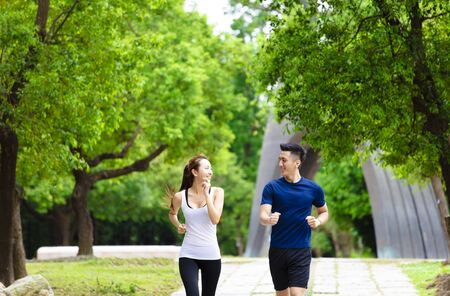 happy Couple jogging and running in nature Stock Photo
