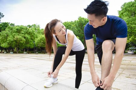 young couple tying running shoes and getting ready to run