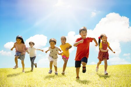 Multi-ethnic group of school children laughing and running Imagens