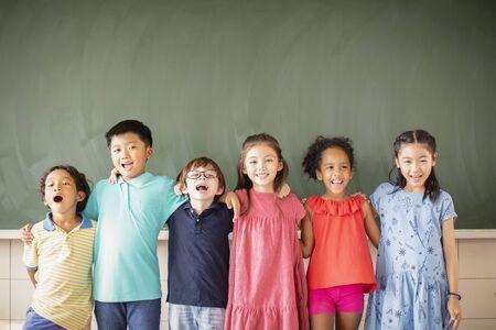 Grupo multiétnico de niños en edad escolar de pie en el aula Foto de archivo