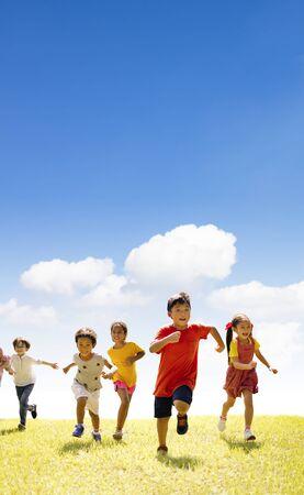 Multiethnic group of school children running on the grass Stock Photo