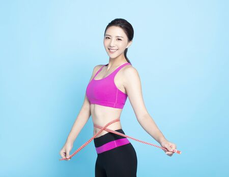 Slim young woman measuring her thin waist with a tape measure