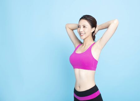 Smiling young fitness woman portrait isolated on blue background Stock fotó