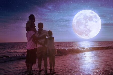 Family standing on beach and watching the moon. Celebrate Mid-autumn festival together
