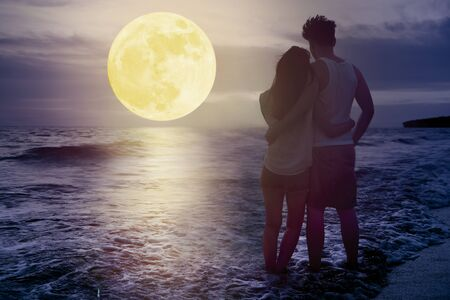 couple standing on beach and watching the moon. Celebrate Mid autumn festival together Stockfoto