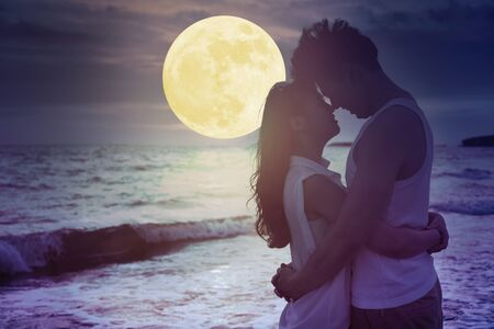young couple kissing on beach and watching the moon.Celebrate Mid autumn festival Stockfoto