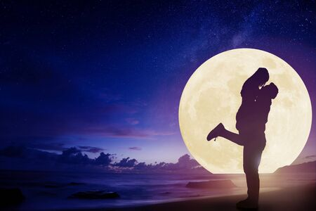 jong koppel zoenen op het strand en kijken naar de maan. Vier het midden van de herfstfestival