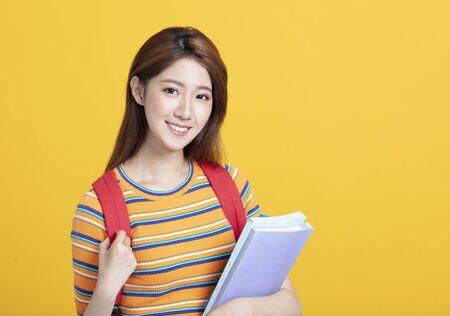 Retrato de hermosa joven estudiante asiática sosteniendo libros Foto de archivo