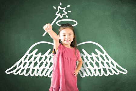 little girl standing against chalkboard and magic   concept