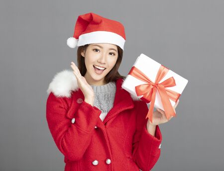 Young Beautiful Woman in winter clothes showing christmas gift 写真素材