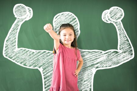 little girl standing against chalkboard and strong winner concept 写真素材