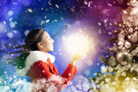 happy young woman watching the light ball and christmas background 写真素材