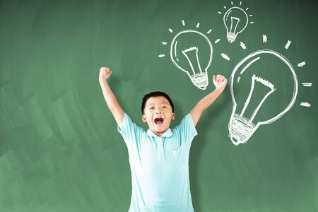 happy asian boy standing against chalkboard with idea bulb concepts