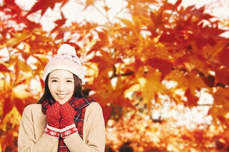 asian Young woman with autumn leaves background Фото со стока