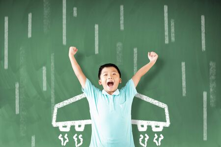 happy little boy standing against chalkboard and airplane  icon on the board