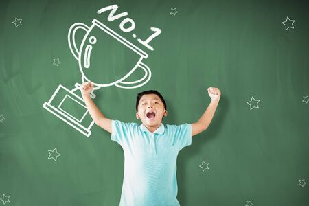 happy little boy standing against chalkboard and showing the champions cup concepts
