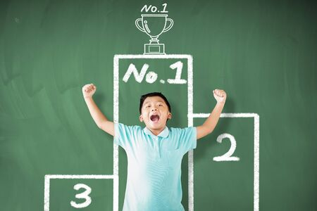 happy  boy standing against chalkboard and showing the champions cup concepts