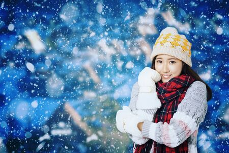 Young Beautiful Woman in winter clothes with snow background