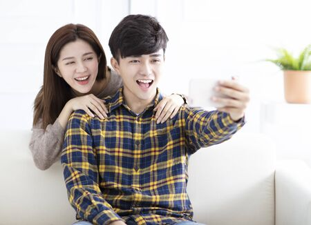 Cheerful young couple taking selfie at home in the morning Reklamní fotografie - 129607362