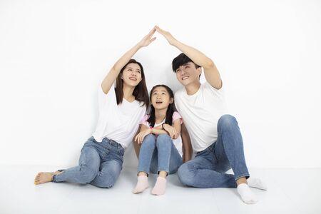 glückliche junge familie, die mit hauskonzept auf dem boden sitzt Standard-Bild