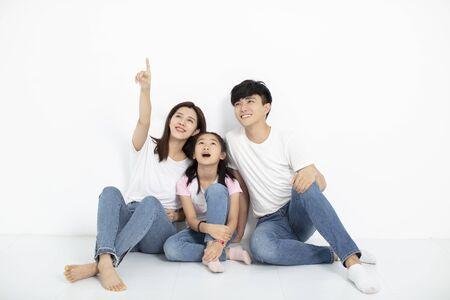 gelukkig jong gezin zittend op de vloer en omhoog kijkend Stockfoto