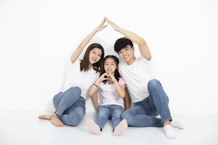 happy young family sitting on floor with home concept 写真素材