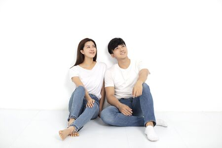 Happy Young Couple Sitting On Floor Looking Up