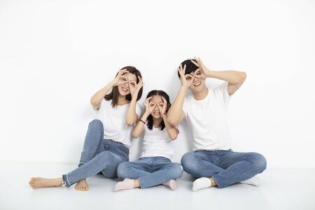 happy young family sitting on floor with looking gesture 写真素材