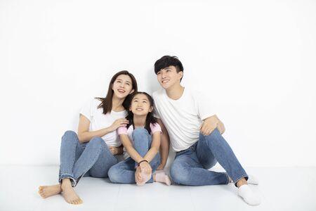 Familia joven feliz sentado en el suelo mirando hacia arriba