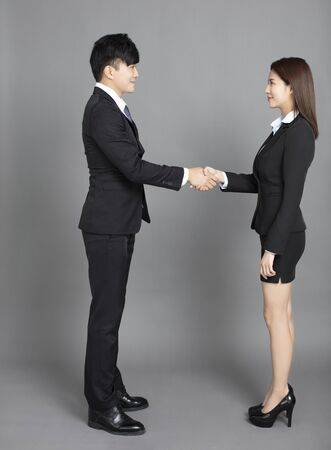 young business man and woman handshaking  against gray background