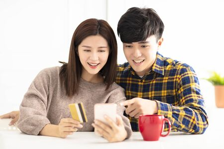 Happy young couple  shopping online by smart phone