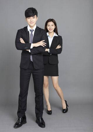 young business man and woman standing against gray background Reklamní fotografie - 129625355