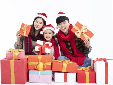 happy family sitting on floor and showing christmas gift