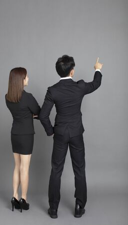 rear view of young business man and woman pointing to gray background