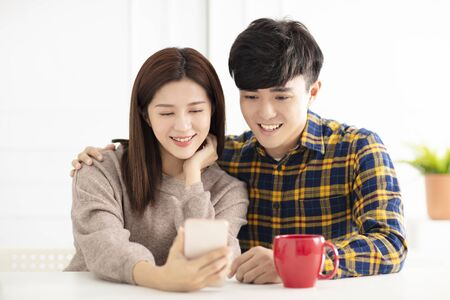 Happy young couple looking at smartphone 写真素材