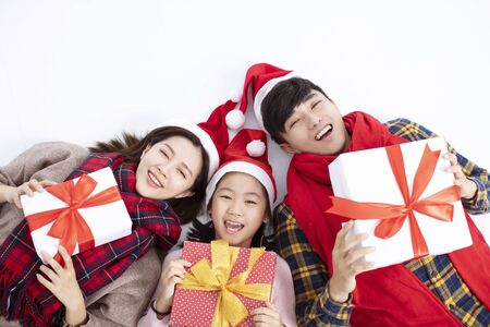 happy family lying on floor and showing christmas gift